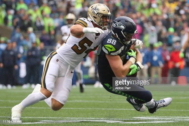 Will Dissly of the Seattle Seahawks completes a pass against Kiko Alonso of the New Orleans Saints in the third quarter during their game at...