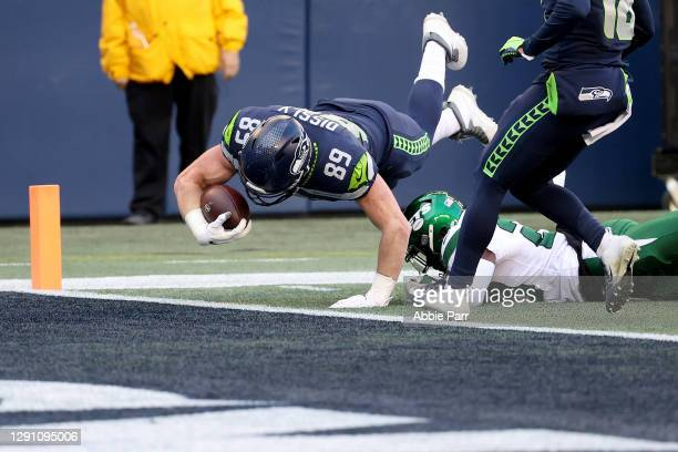 Will Dissly of the Seattle Seahawks dives in the end zone to score a 10 yard touchdown against the New York Jets in the game at Lumen Field on...