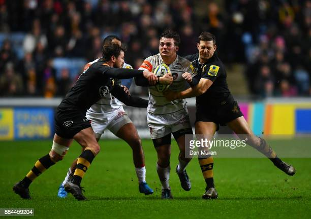 Will Evans of Leicester Tigers is tackled by Danny Cipriani and Jimmy Gopperth of Wasps during the Aviva Premiership match between Wasps and...