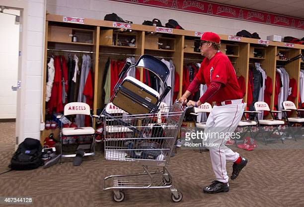 Will Ferrell pushes a cart of items out of the clubhouse of the Los Angeles Angels of Anaheim during the spring training game between the Chicago...