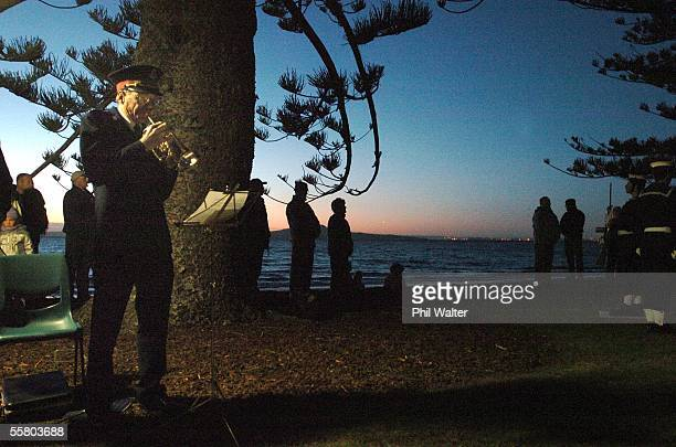 Will Fordyce plays the last post on his bugle as the sun rises over the Cenotaph on Browns Bay beach on Aucklands North Shore New Zealand Monday...