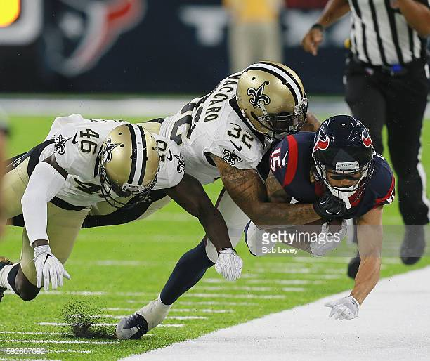 Will Fuller of the Houston Texans is tackled out of bounds by Kenny Vaccaro of the New Orleans Saints and Ken Crawley during a preseason NFL game at...