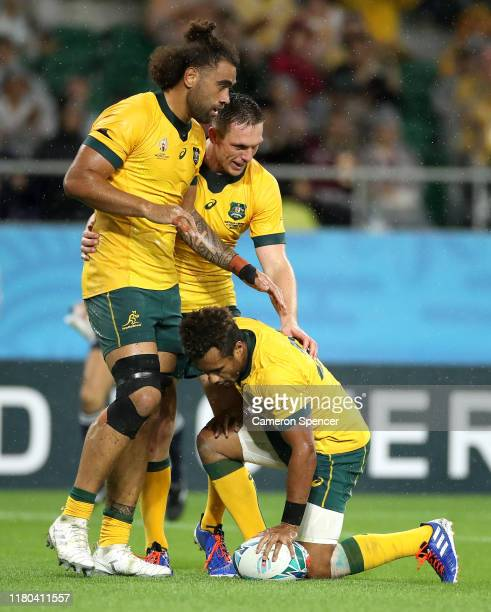 Will Genia of Australia celebrates with teammates Dane Haylett-Petty and Lukhan Salakaia-Loto of Australia after scoring his teams fourth try during...