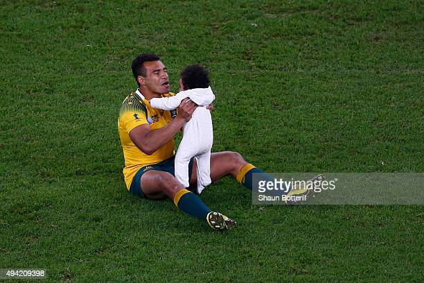 Will Genia of Australia sits on the field with his daughter Olivia during the 2015 Rugby World Cup Semi Final match between Argentina and Australia...