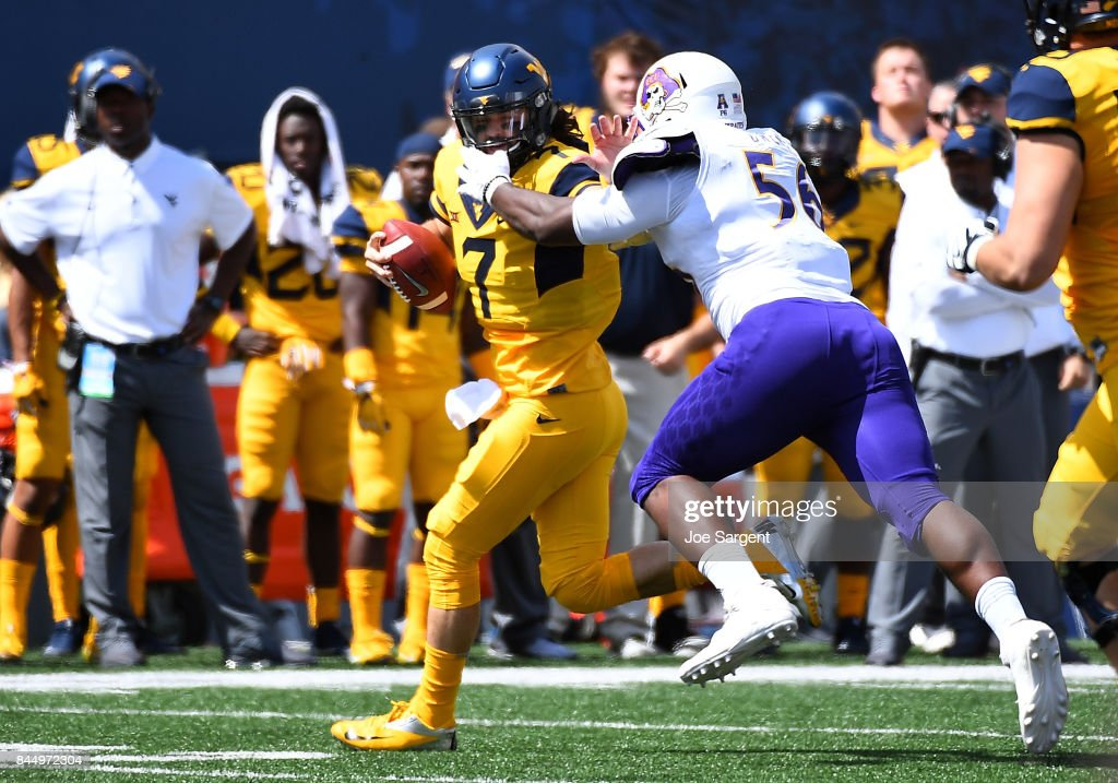 Will Grier #7 of the West Virginia Mountaineers draws a face masking penalty while trying to avoid a tackle by Tyree Owens #56 of the East Carolina Pirates during the second quarter at Mountaineer Field on September 9, 2017 in Morgantown, West Virginia.
