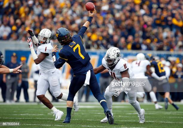 Will Grier of the West Virginia Mountaineers gets a pass on under pressure from Amen Ogbongbemiga of the Oklahoma State Cowboys at Mountaineer Field...