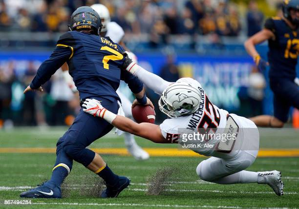 Will Grier of the West Virginia Mountaineers is sacked by Cole Walterscheid of the Oklahoma State Cowboys at Mountaineer Field on October 28 2017 in...