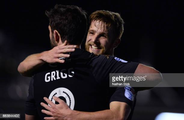 Will Grigg hugs Michael Jacobs of Wigan Athletic after he scores during The Emirates FA Cup Second Round match between AFC Fylde and Wigan Athletic...