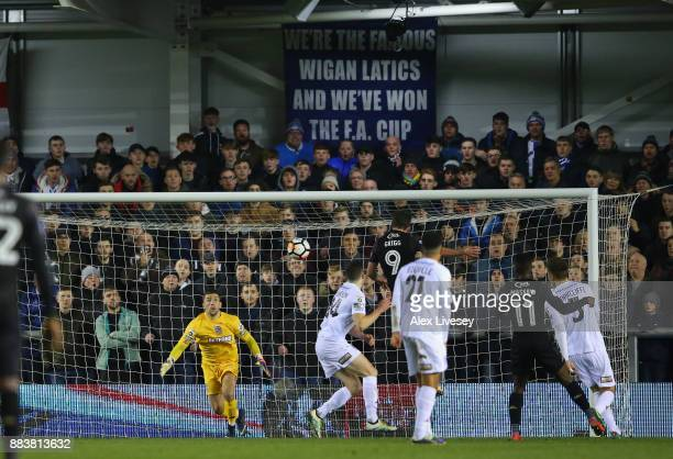 Will Grigg of Wigan Athletic scores the opening goal past Jay Lynch of AFC Fylde with a header during The Emirates FA Cup Second Round between AFC...