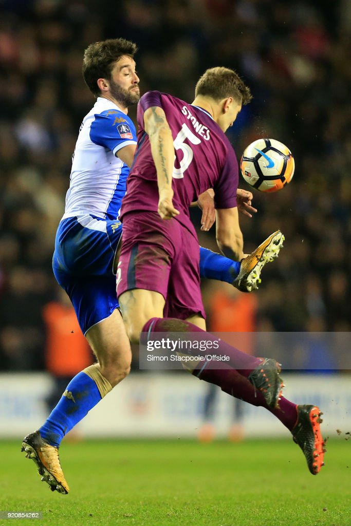 Will Grigg of Wigan battles with John Stones of Man City during The Emirates FA Cup Fifth Round match between Wigan Athletic and Manchester City at the DW Stadium on February 19, 2018 in Wigan, England.