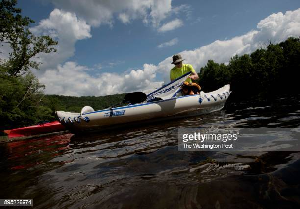 Will Hackman of Washington DC steadies his inflatable kayak before launching down the Potomac river for a twoday paddle Members and friends of the...