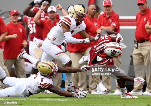 Will Harris and Hamp Cheevers of the Boston College Eagles tackle Reggie Gallaspy II of the North Carolina State Wolfpack during their game at...