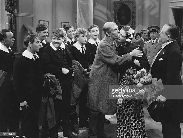 Will Hay gives a lady a kiss to the amusement of Graham Moffat and a group of schooboys in a scene from the film 'Good Morning Boys' directed by...