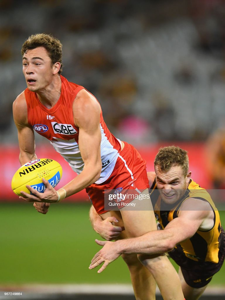 Will Hayward of the Swans handballs whilst being tackled by Tom Mitchell of the Hawks during the round eight AFL match between the Hawthorn Hawks and the Sydney Swans at Melbourne Cricket Ground on May 11, 2018 in Melbourne, Australia.