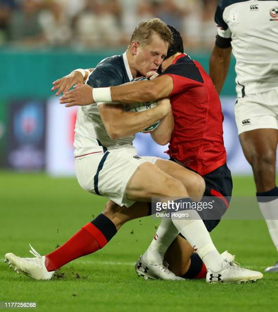 Will Hooley of the USA is tackled by Piers Francis in the first minute during the Rugby World Cup 2019 Group C game between England and USA at Kobe...