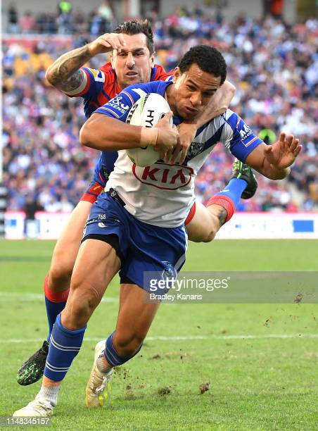 Will Hopoate of the Bulldogs attempts to break away from the defence of Mitchell Pearce of the Knights during the round nine NRL match between the...