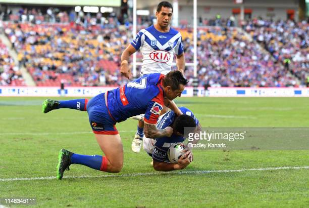 Will Hopoate of the Bulldogs breaks away from the defence of Mitchell Pearce of the Knights to score a try during the round nine NRL match between...