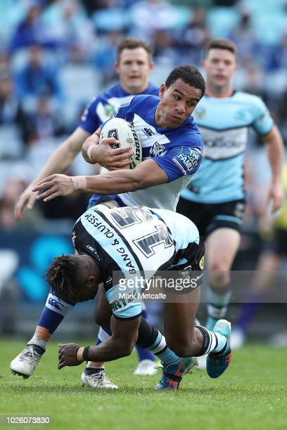 Will Hopoate of the Bulldogs fends off James Segeyaro of the Sharks during the round 25 NRL match between the Canterbury Bulldogs and the Cronulla...