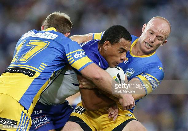 Will Hopoate of the Bulldogs is tackled by Beau Scott and David Gower of the Eels during the round three NRL match between the Canterbury Bulldogs...