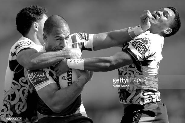 Will Hopoate of the Bulldogs is tackled by Hayze Perham and Paul Turner of the Warriors during the round eight Super Rugby AU match between the...