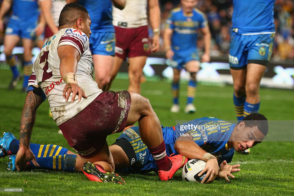 Will Hopoate of the Eels scores a try under pressure from Jorge Taufua of the Sea Eagles during the round 24 NRL match between the Parramatta Eels and the Manly Sea Eagles at Pirtek Stadium on August 22, 2014 in Sydney, Australia.
