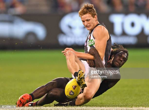 Will HoskinElliott of the Magpies kicks whilst being tackled by Anthony McDonaldTipungwuti of the Bombers during the round five AFL match between the...