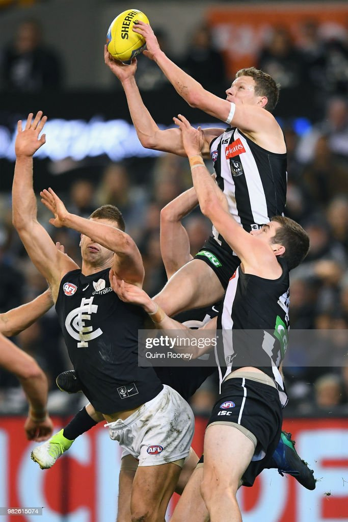 Will Hoskin-Elliott of the Magpies marks over the top of Liam Jones of the Blues during the round 14 AFL match between the Collingwood Magpies and the Carlton Blues at Melbourne Cricket Ground on June 24, 2018 in Melbourne, Australia.