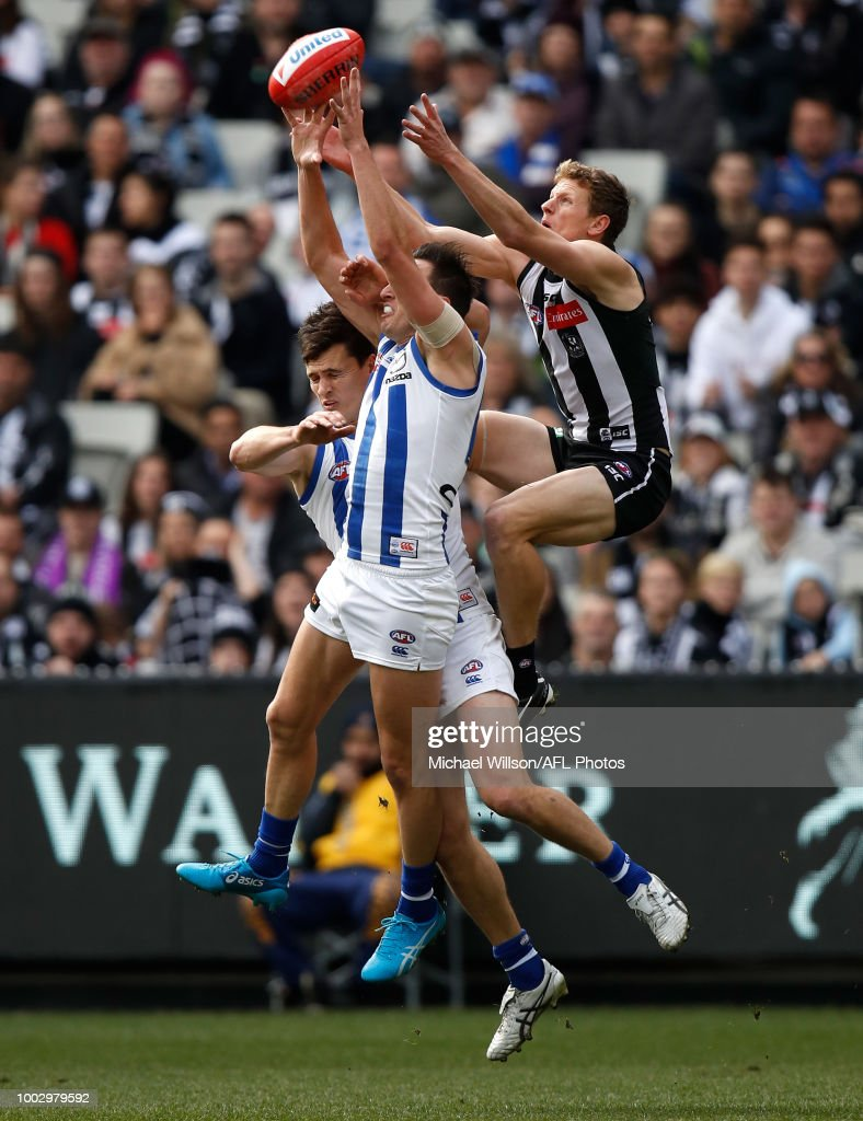 Will Hoskin-Elliott of the Magpies ties a spectacular mark over Scott Thompson of the Kangaroos and Sam Wright of the Kangaroos during the 2018 AFL round 18 match between the Collingwood Magpies and the North Melbourne Kangaroos at the Melbourne Cricket Ground on July 21, 2018 in Melbourne, Australia.