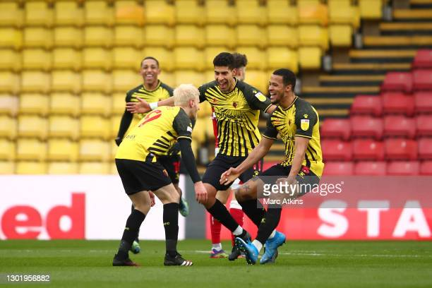 Will Hughes of Watford celebrates with teammates Adam Masina and William Troost-Ekong after scoring his team's third goal during the Sky Bet...