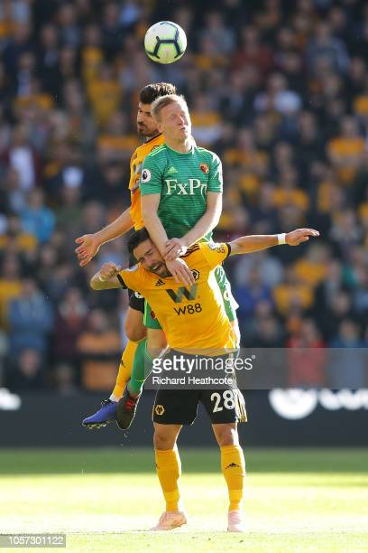 Will Hughes of Watford wins a header between Ruben Neves and Joao Moutinho of Wolves during the Premier League match between Wolverhampton Wanderers...