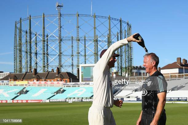 Will Jacks pours champagne over Alec Stewart of Surreyas they celebrates winning the Specsavers County Championship Division One Cup during Day Four...