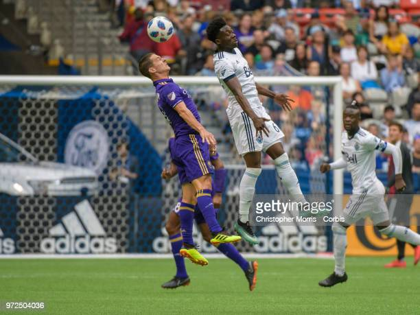 Will Johnson of Orlando City and Alphonso Davies of the Vancouver Whitecaps fight for the ball during a match between Orlando City SC and Vancouver...