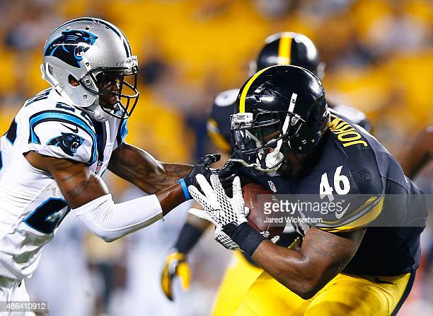 Will Johnson of the Pittsburgh Steelers has his facemask grabbed while running with the ball in the fourth quarter by TJ Heath of the Carolina...