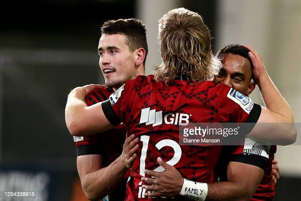 Will Jordan of the Crusaders celebrates his try with team-mates Jack Goodhue and Sevu Reece during the round 4 Super Rugby Aotearoa match between the...