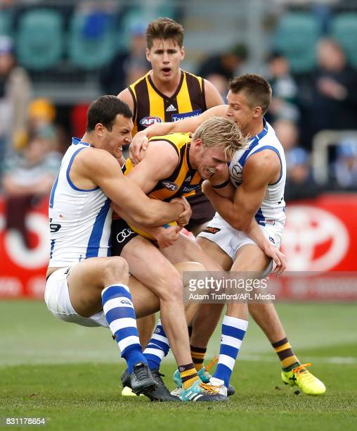 Will Langford of the Hawks is tackled by Braydon Preuss and Andrew Swallow of the Kangaroos during the 2017 AFL round 21 match between the Hawthorn...