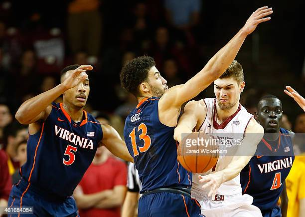 WIll Magarity of the Boston College Eagles is defended by Anthony Gill of the Virginia Cavaliers in the first half during the game at Conte Forum on...
