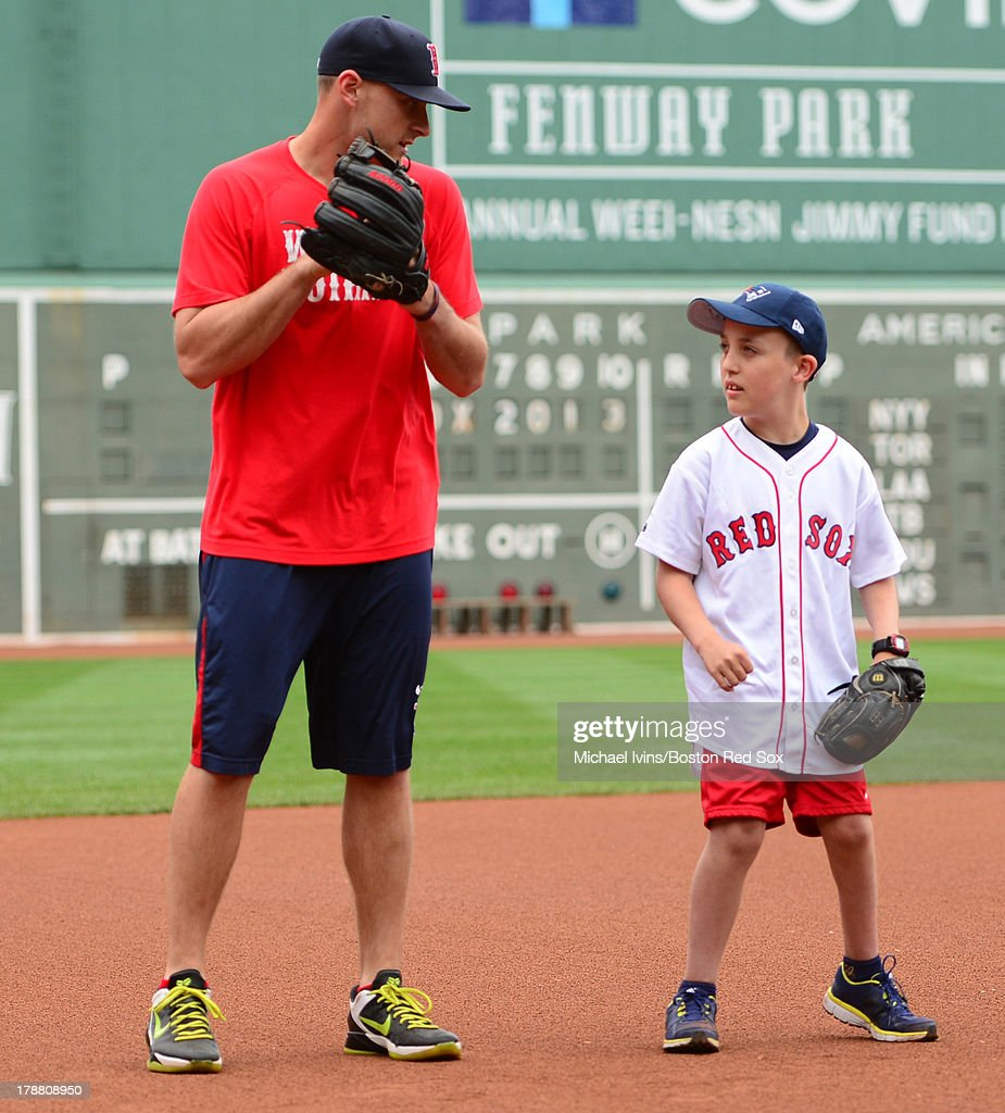 Will Middlebooks #16 of the Boston Red Sox gives a private fielding lesson to Alex Yood, 12, before a game against the Baltimore Orioles on August 29, 2013 at Fenway Park in Boston Massachusetts.