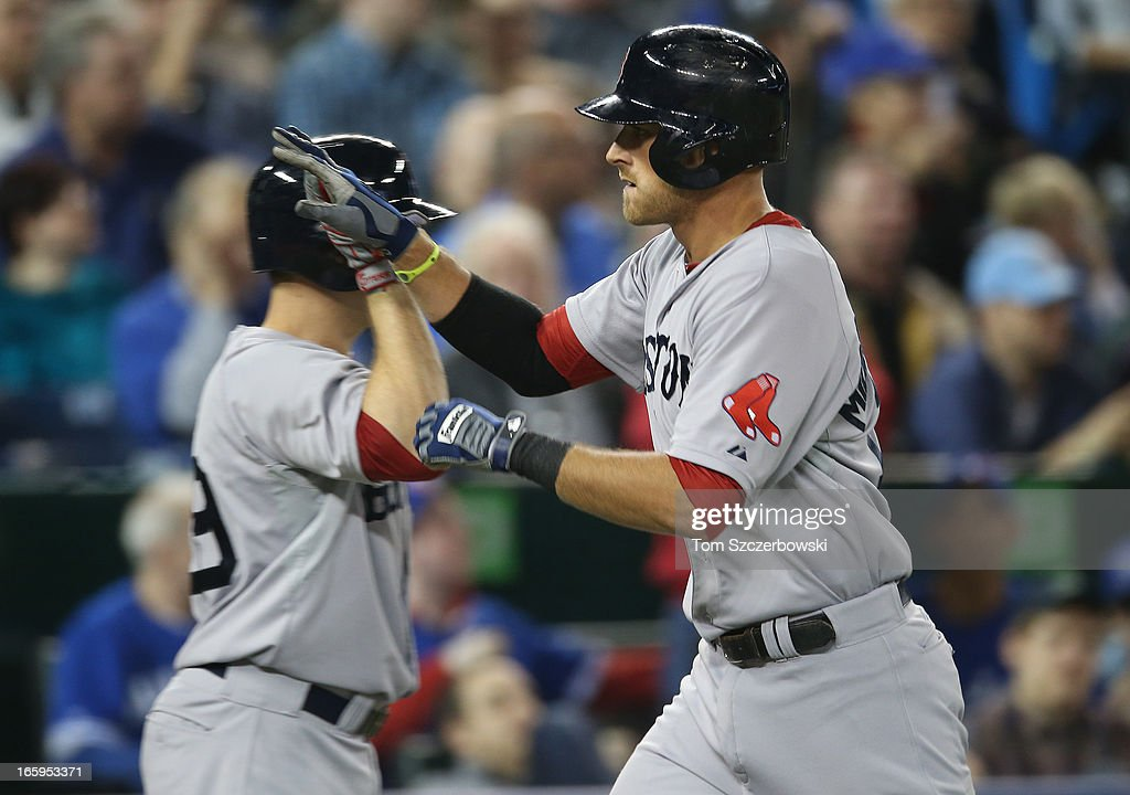 Will Middlebrooks #16 of the Boston Red Sox is congratulated by Daniel Nava #29 after hitting a home run in the fifth inning during MLB game action against the Toronto Blue Jays on April 7, 2013 at Rogers Centre in Toronto, Ontario, Canada.