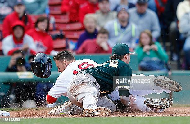Will Middlebrooks of the Boston Red Sox is tagged out by Josh Donaldson of the Oakland Athletics attempting to move to third on a ball hit byJackie...
