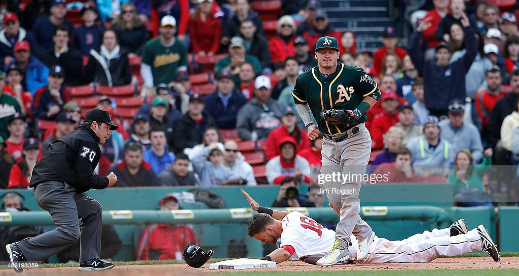 Will Middlebrooks #16 of the Boston Red Sox reacts after he was tagged out by Josh Donaldson #20 of the Oakland Athletics attempting to move to third on a ball hit by Jackie Bradley Jr. #25 in the tenth inning at Fenway Park on May 4, 2014 in Boston, Massachusetts.