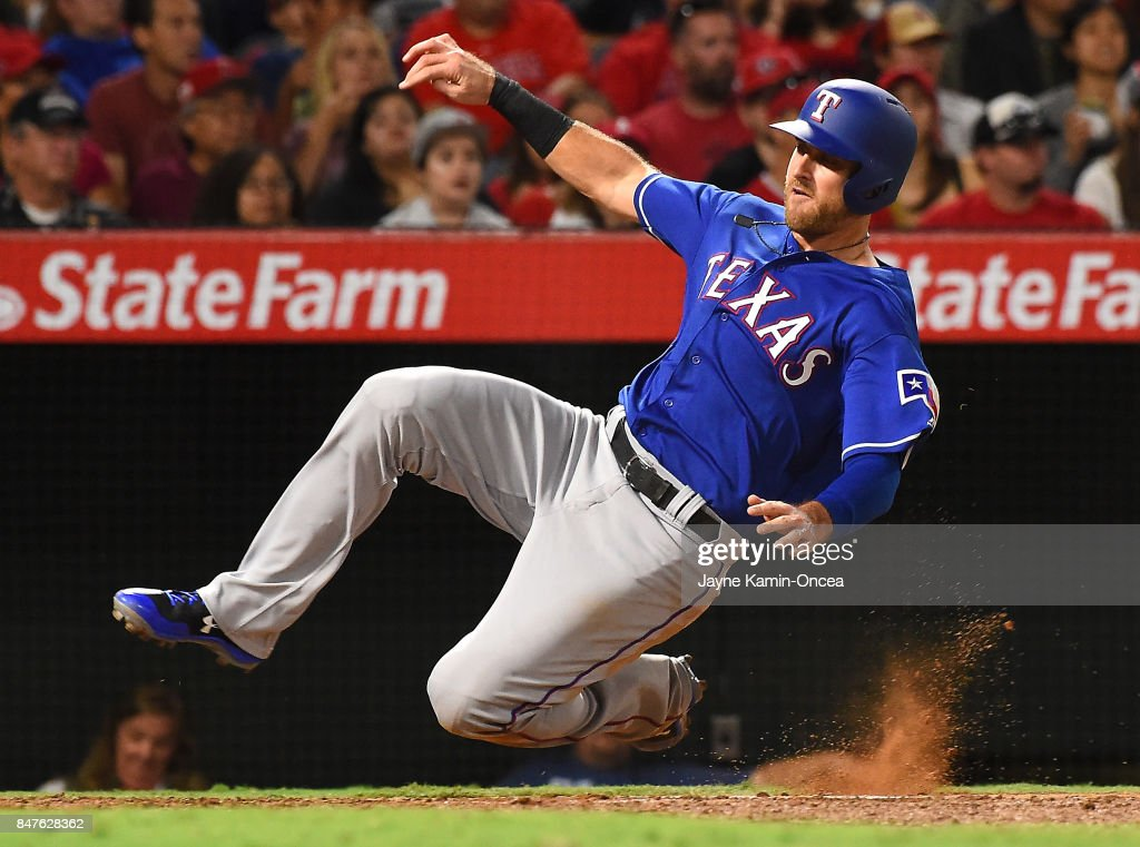 Will Middlebrooks #15 of the Texas Rangers slides into home to score a run in the fifth inning of the game against the Los Angeles Angels of Anaheim at Angel Stadium of Anaheim on September 15, 2017 in Anaheim, California.