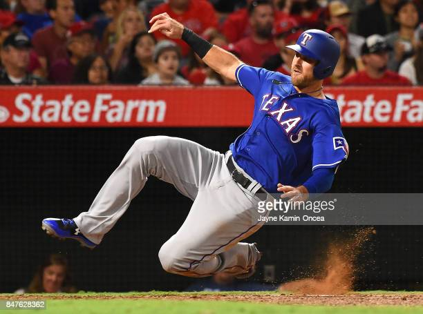 Will Middlebrooks of the Texas Rangers slides into home to score a run in the fifth inning of the game against the Los Angeles Angels of Anaheim at...