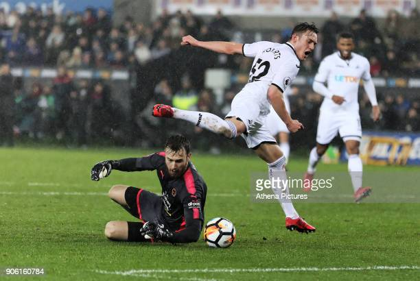 Will Norris of Wolverhampton Wanderers slides to grab the ball while Connor Roberts of Swansea City jumps over him during the Emirates FA Cup match...