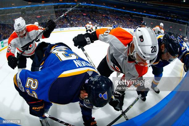 Will O'Neill and Taylor Leier of the Philadelphia Flyers fight Dmitrij Jaskin and Scottie Upshall of the St Louis Blues for control of the puck at...