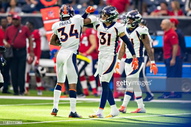 Will Parks and Justin Simmons of the Denver Broncos celebrate after Parks intercepts a pass during the second half of a game against the Houston...