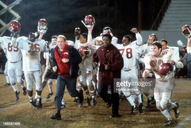 Will Patton and Denzel Washington run out onto the field in a scene form the film 'Remember The Titans' 2000