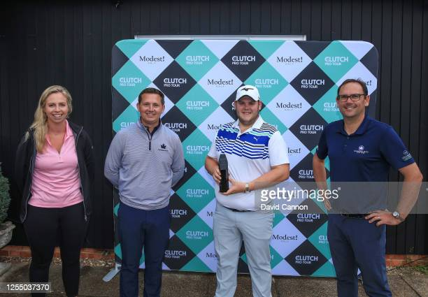 Will Percival of England holds the winner's trophy after his playoff win with Kate Hall from Modest Golf Tom Reid the head professional at...