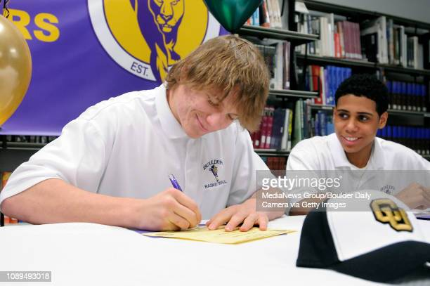 Will Pericak signs his name on his letter of intent to the University of Colorado for a National Signing Day ceremony as teammate JB Hall watches at...