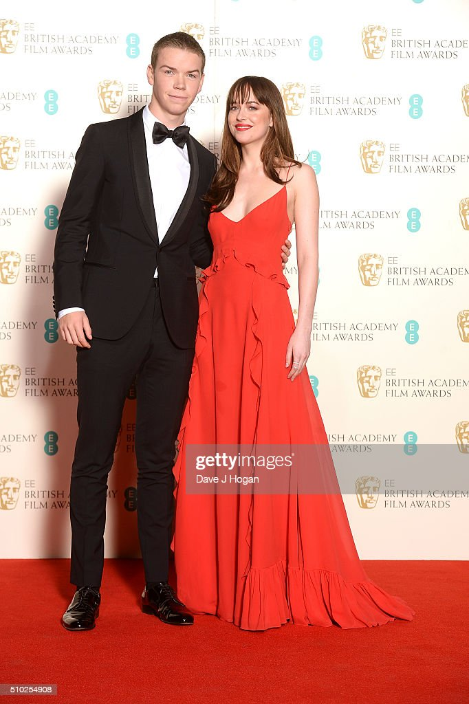 Will Poulter (L) and Dakota Johnson pose in the winners room at the EE British Academy Film Awards at The Royal Opera House on February 14, 2016 in London, England.