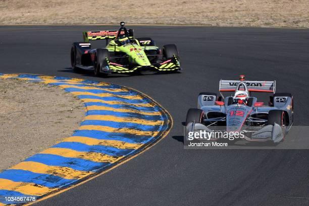 Will Power driver of the Team Penske Chevrolet races against Sebastien Bourdais driver of the Dale Coyne Racing with VasserSullivan Honda during the...
